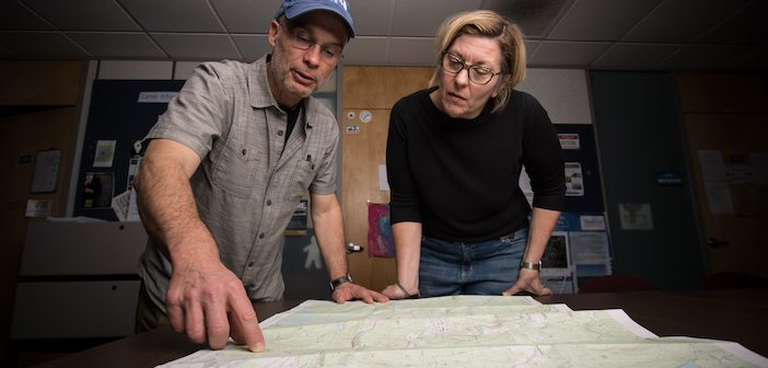 Westfield State University faculty member Carsten Braun (l) and student Stacey Dakai looking over a traditional 2D paper map in the GIS office at the University.