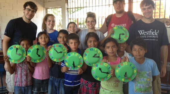 Student with Nicaraguan children holding up hand made clocks