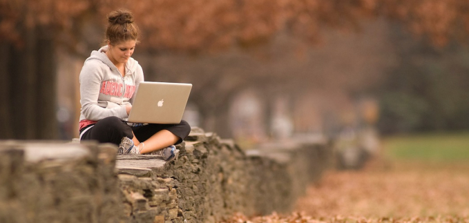 Female student studies on a stone wall