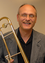 A portrait of a man holding a trombone