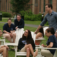 students sitting in chairs on the green